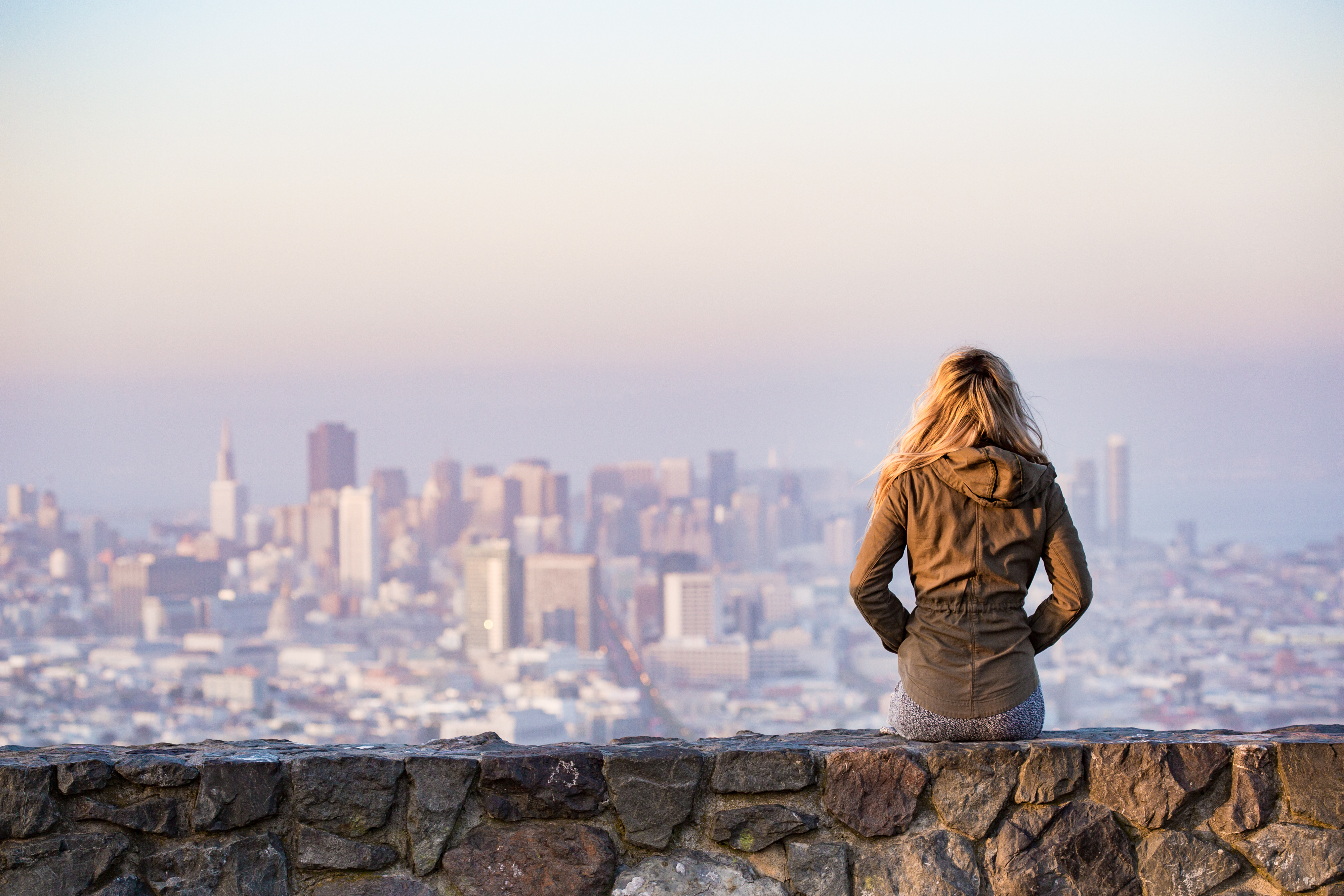 girl-in-coat-sits-on-stone-wall-with-city-view-in-the-distance